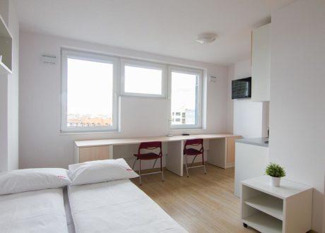 Meble na zamówienie dla mikroapartamentu Starter we Wrocławiu. W skład zestawu mebli wchodzi: sofa, szafy, stolik, biurko, aneks kuchenny, krzesła - MIKROAPARTAMENTY I HOTELE