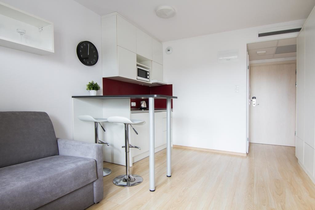 Meble na zamówienie dla mikroapartamentu Starter we Wrocławiu. W skład zestawu mebli wchodzi: sofa, szafy, stolik, biurko, aneks kuchenny, krzesła