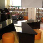 Meble na zamówienie dla biblioteki. Wyposażenie: sofa, regały biblioteczne, szafy, stolik, biurko, fotele, krzesła, lada biblioteczna